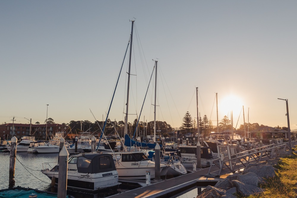[Image Description: white boats in a marina, rocks and ramps surrounding the area, blue sky above and sun setting in the middle right side of image.]